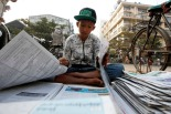A boy selling newspapers folds them before selling them in Yangon